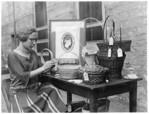 Woman placing tags on baskets, 1925