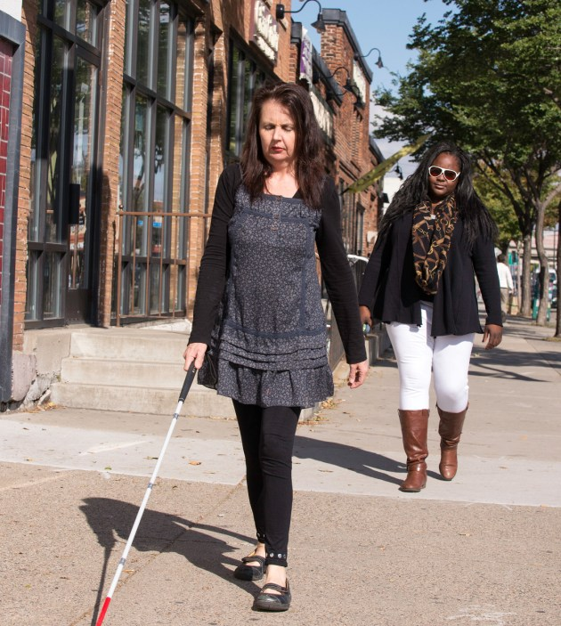 woman walking with white cane, instructor behind her