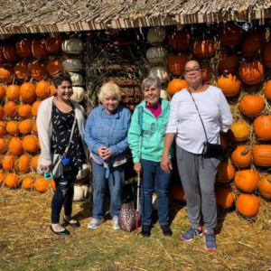Clients and volunteers standing in front of a log cabin stacked with pumpkins