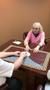 Linda guiding a man to feel a tactile work of art on a table